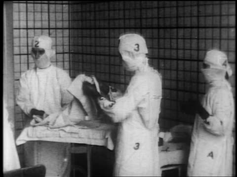 b/w 1910s/20s ms doctors + nurse with numbers + letters on gowns preparing medical supplies - prelinger archive video stock e b–roll