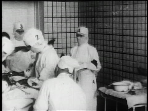 b/w 1910s/20s ms doctors + nurses with letters + numbers on gowns performing surgery - 1910 stock-videos und b-roll-filmmaterial