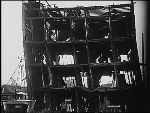 B/W 1910s/20s gutted shell of building collapsing / newsreel