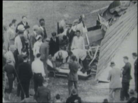 b/w 1910s/20s high angle crowd putting injured pilot on stretcher - stunt stock videos & royalty-free footage