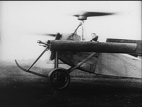 stockvideo's en b-roll-footage met b/w 1910s/20s pan man attempting to take off in early airplane with rotors on wings - ouderwets
