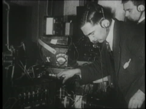 B/W 1910s/20s man wearing headphones + operating early radio station