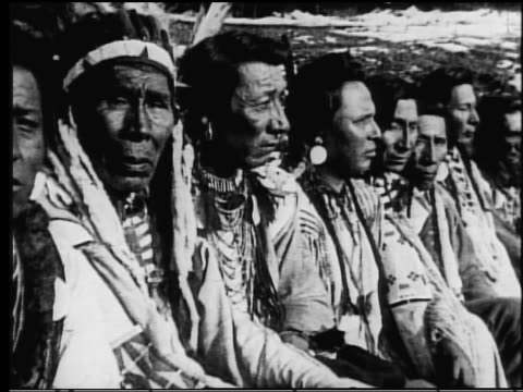 b/w 1910s/20s ms portrait line of native americans turning heads towards camera outdoors - tribù del nord america video stock e b–roll