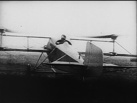 B/W 1910s/20s REAR VIEW man attempting to take off in early airplane with rotors on wings
