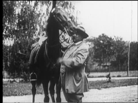 B/W 1910s/20s MS Teddy Roosevelt standing by horse petting it then leading it off camera