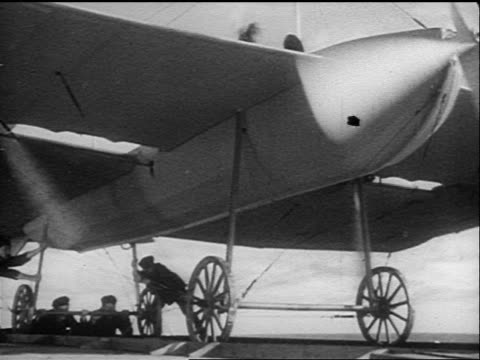B/W 1910s/20s underside of early steam powered aircraft with engines running / men holding it down