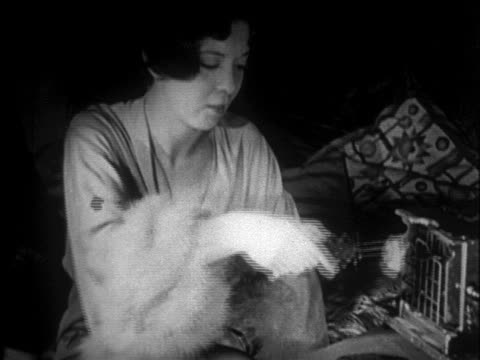b/w 1920s 2 flappers toasting marshmallows indoors with electric toaster + marshmallow holder - marshmallow video stock e b–roll