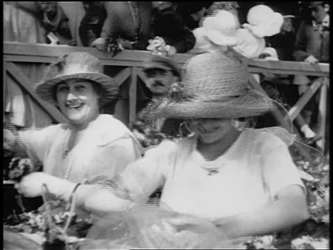 vidéos et rushes de b/w 1920s 2 laughing women throwing flowers on city street / paris / documentary - chapeau de paille