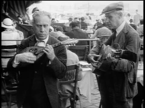 vídeos de stock e filmes b-roll de b/w 1920s 2 senior men playing musical instruments at crowded outdoor cafe / paris / documentary - café edifício de restauração