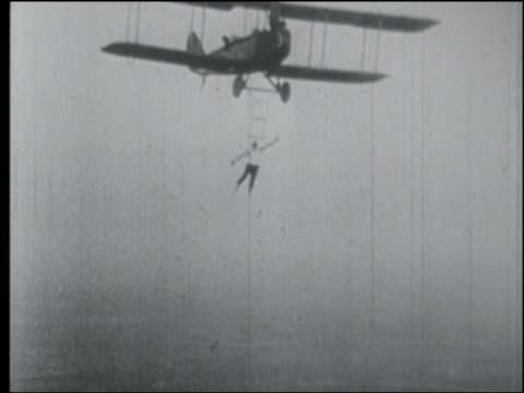 b/w 1920s aerial man hanging from biplane in air by head - stunt person stock videos & royalty-free footage