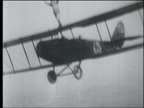 b/w 1920s aerial man standing on top of biplane flying in air - 若い男性だけ点の映像素材/bロール
