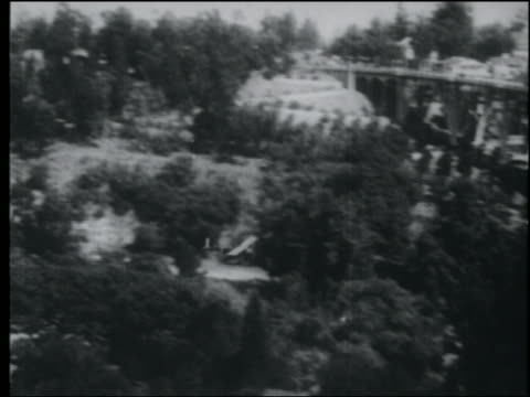 B/W 1920s AERIAL over biplane piloted by Art Goebels flying underneath highway