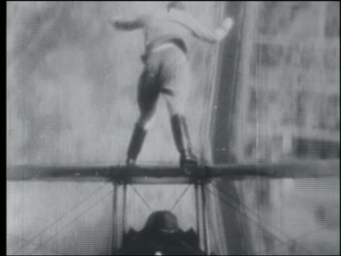b/w 1920s aerial point of view rear view man standing on top of biplane doing circles in air - stunt person stock videos & royalty-free footage