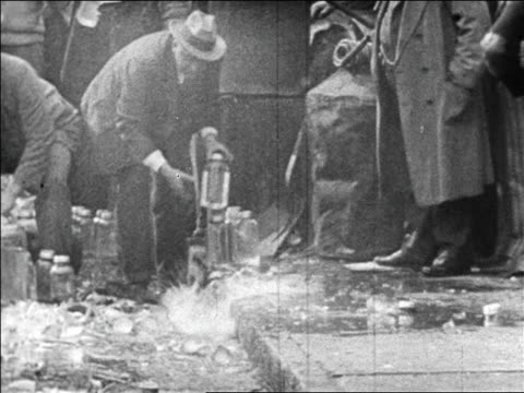 stockvideo's en b-roll-footage met 1920s authorities smashing bottles of bootleg liquor on curb / prohibition / newsreel - 1920