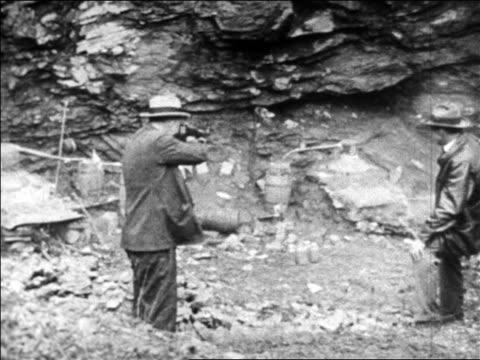 B/W 1920s authority pointing gun at barrel of bootleg liquor / Prohibition / newsreel