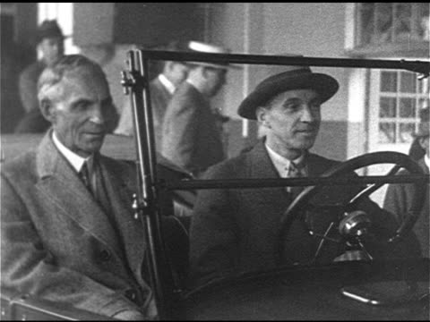 vidéos et rushes de auto industry la ws 15 millionth model t automobile car at end of production line henry ford sitting in car w/ unidentified male driving car off... - ford model t