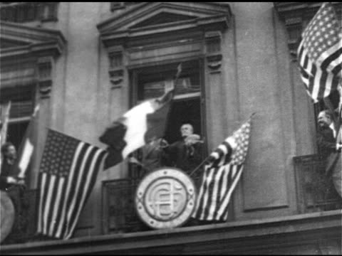 AVIATION American aviator Charles Lindbergh standing in open window holding large American French flags TD WS Waving crowd CU Charles Lindbergh...