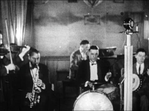 B/W 1920s band playing into microphone in radio studio