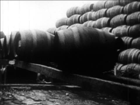 vidéos et rushes de 1920s barrels of bootleg liquor rolling down plank / prohibition / newsreel - b roll