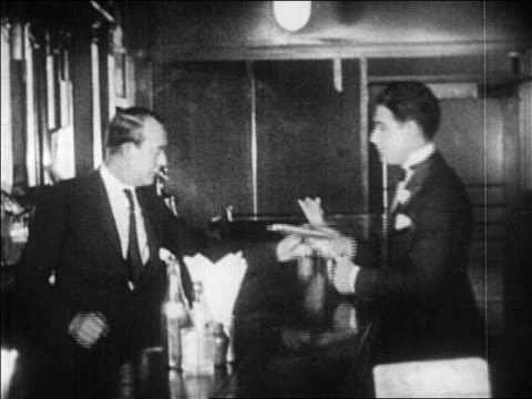 vídeos de stock, filmes e b-roll de b/w 1920s bartender handing man flask of liquor at bar in speakeasy / prohibition / newsreel - abuso de substâncias
