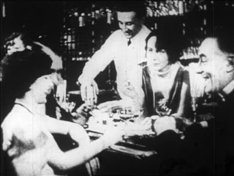 b/w 1920s bartender serving people standing at bar in speakeasy / prohibition / newsreel - 禁酒法点の映像素材/bロール