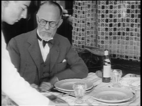 vidéos et rushes de b/w 1920s bearded man being served by waiter at outdoor restaurant / paris / documentary - stéréotype de la classe supérieure