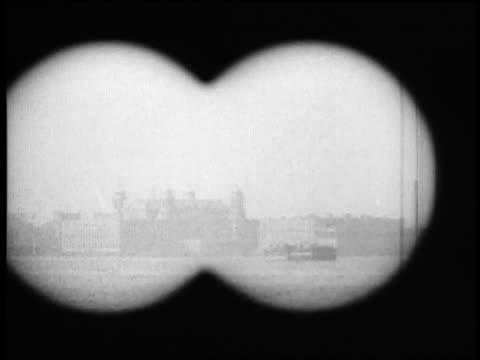 B/W 1920s binoculars point of view from boat of Ellis Island / NYC / documentary