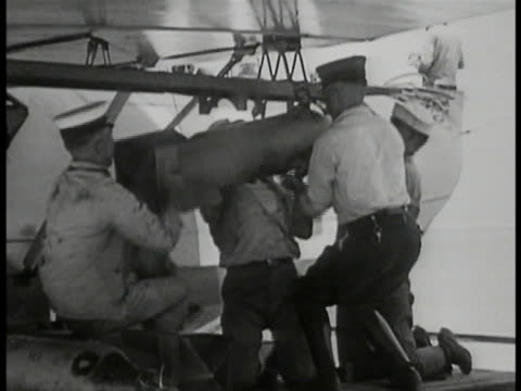biplane bomber officer standing next to airplane w/ bird of prey insignia sailors mounting bomb under aircraft xws biplane taking off from carrier... - insignia stock videos and b-roll footage