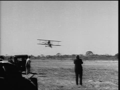 b/w 1920s pan bi-plane with tricycle landing gear landing in grassy field - プロペラ機点の映像素材/bロール