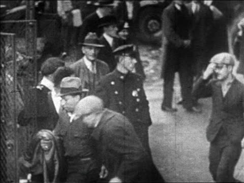 B/W 1920s bootleggers being escorted into paddy wagon / Prohibition / newsreel