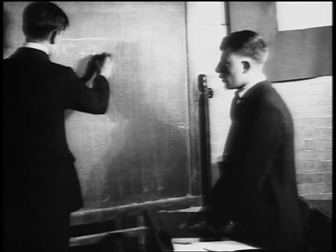 b/w 1920s boy doing math problems at chalkboard as other boy watches in vocational school / newsreel - mathematics stock videos & royalty-free footage