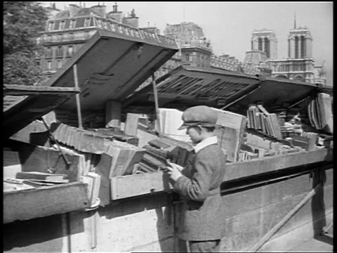 B/W 1920s boy with hat looking at books at outdoor book stall / Paris / documentary