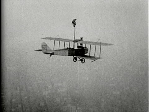 1920s b/w aerial, composite, man perched atop pole attached to biplane flying above city, ts - stunt stock-videos und b-roll-filmmaterial