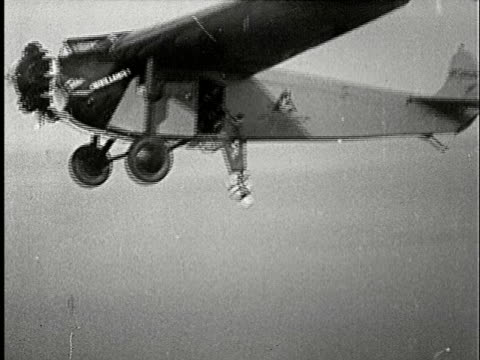 1920s b/w aerial, ts, man getting on plane wearing straightjacket, freeing himself out of it while hanging on rope mid air, composite - hanging stock videos & royalty-free footage