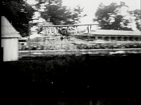1920s b/w ms, pan, biplane crushing into barn on landing - airplane crash stock videos and b-roll footage