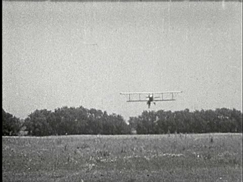 1920s b/w ms, pan, biplane landing on field with man hanging on landing wheels - 1920 stock videos & royalty-free footage