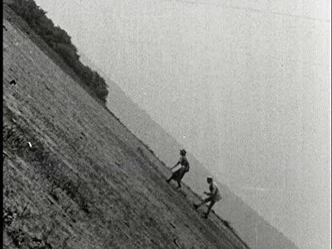 vídeos de stock, filmes e b-roll de 1920s b/w ms, composite, couple walking on field - inclinação