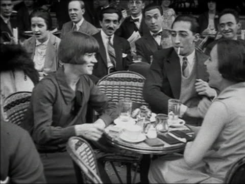 1920s b/w ms man and two women at outdoor cafe laughing and smoking / paris, france - sigaretta video stock e b–roll