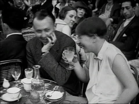vidéos et rushes de 1920s b/w ha ms man and woman talking and laughing at outdoor cafe with women in background / paris, france - 1920