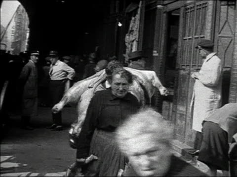 1920s b/w ms pan man carrying pig carcass through busy city street / paris, france - maiale ungulato video stock e b–roll
