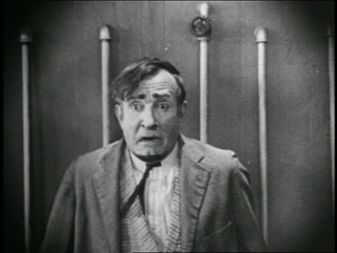 1920s B/W CU Man (Charlie Murray) standing while tied to boiler pipes, looking up and reacting in fear to something offscreen / USA