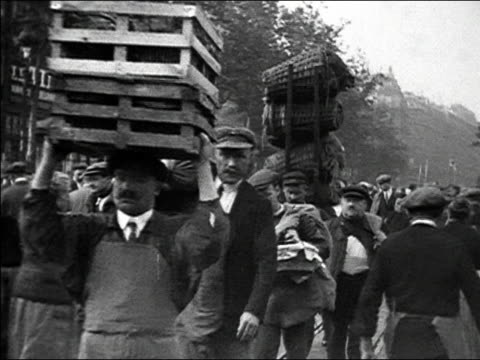 1920s b/w ms men carrying crates through busy city market / paris, france - incidental people stock videos & royalty-free footage