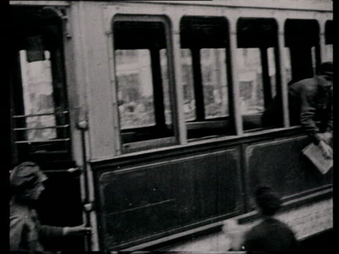 stockvideo's en b-roll-footage met 1920s b/w montage ms ws pov person posting poster on wall crowd gathering reading anouncement film director dziga vertov reading newspaper in tram... - kassei