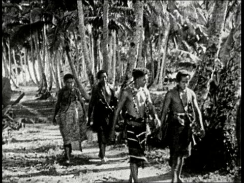 1920s b/w montage samoan wedding guests in a variety of costumes arrive on foot and by boat to wedding ceremony in samoa south seas - isole del pacifico video stock e b–roll