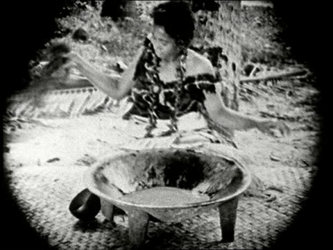 stockvideo's en b-roll-footage met 1920s b/w montage samoan wedding seated woman prepares traditional ava drink by squeezing shrub root in bowl of water / men fling root overhead samoa... - samoa