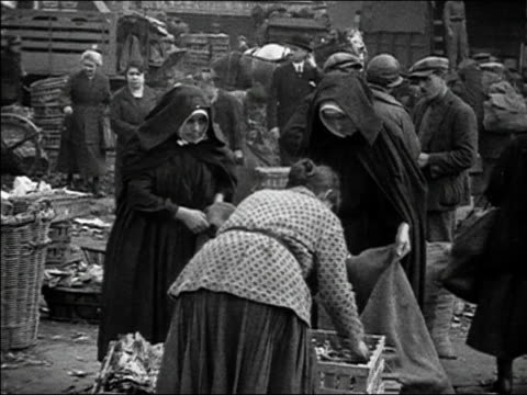vídeos de stock, filmes e b-roll de 1920s b/w ms nuns shopping at street market / paris, france - nun