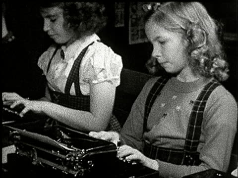 1920s B/W MS, Row of children (10-11) typing on typewriters sitting in classroom