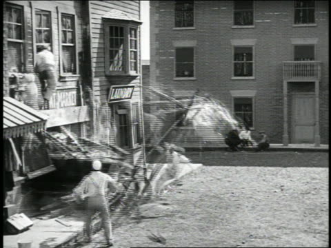b/w 1920s car crashing out of building + knocking over painters / feature - unfall und katastrophe stock-videos und b-roll-filmmaterial