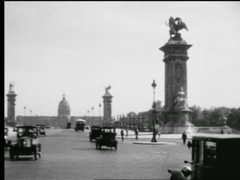 B/W 1920s car point of view in traffic across Pont Alexandre III toward Hotel des Invalides / Paris, France