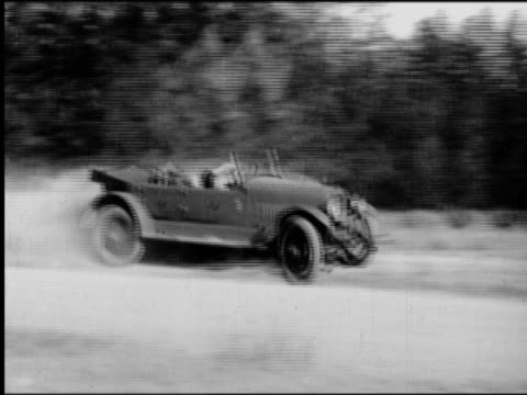 B/W 1920s PAN car speeding on dirt road flipping + crashing into fleeing film crew